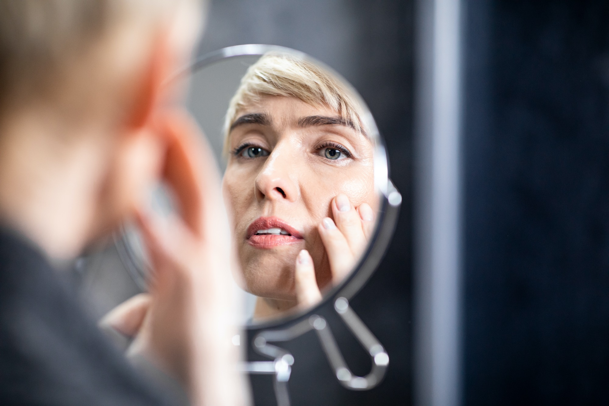 middle-aged-lady-looking-in-mirror-at-wrinkles
